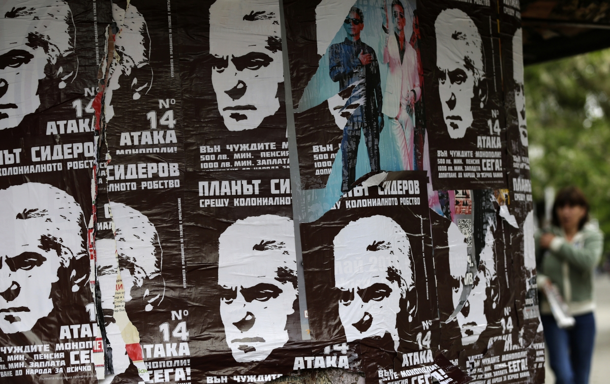 A woman walks past election posters of Volen Siderov, leader of the Attack party, in Sofia