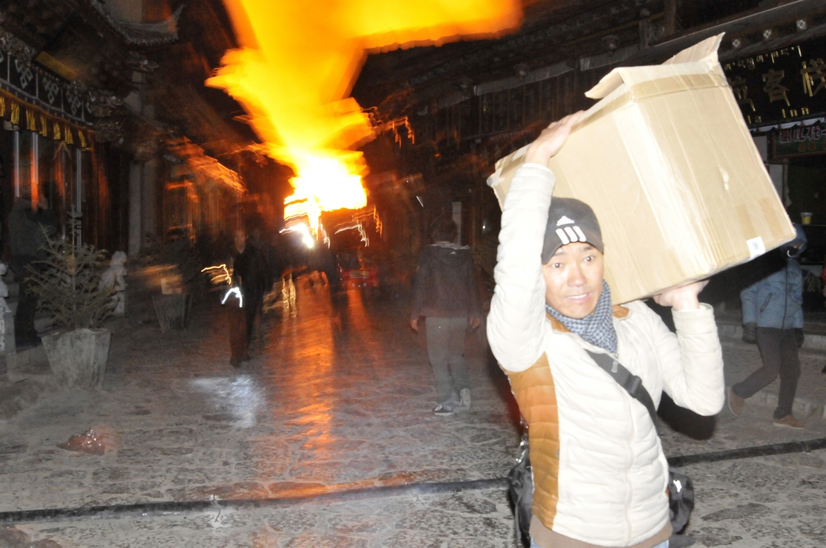 A man carrying his belongings, runs away from a fire at the Dukezong Ancient Town in Shangri-la county.