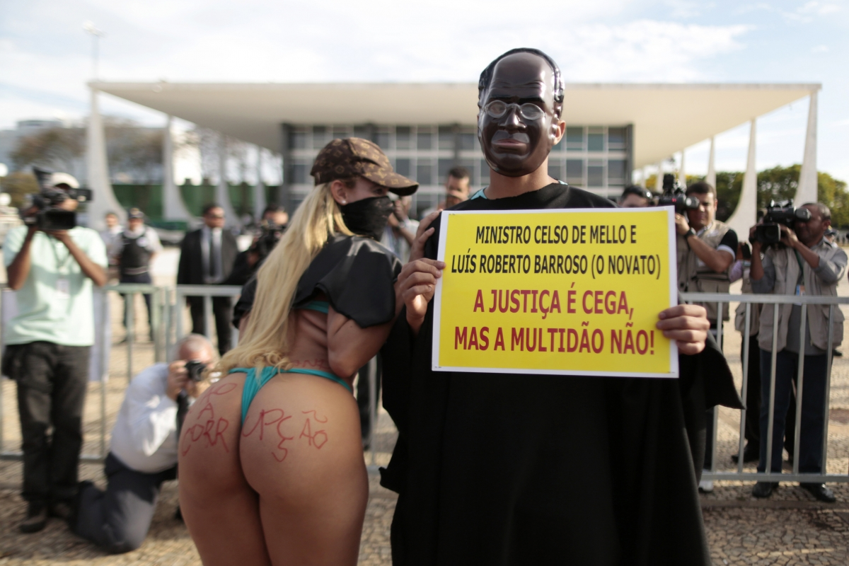 Protesters, dressed as President of Supreme Court Joaquim Barbosa and singer MC Bandida, pose as they protest in front of the Federal Supreme Court of Brazil during the 'mensalao' corruption trials.  The poster reads,