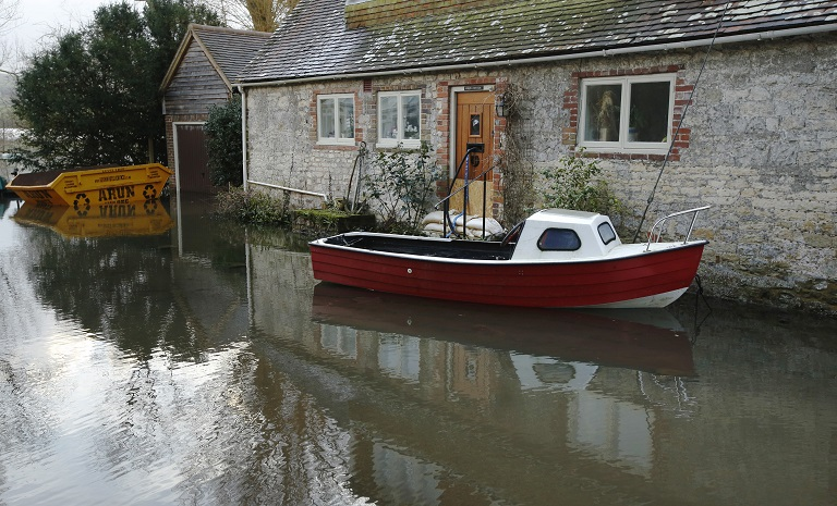 A boat floats in front of a house during flooding at Bury near Pulborough in southern England