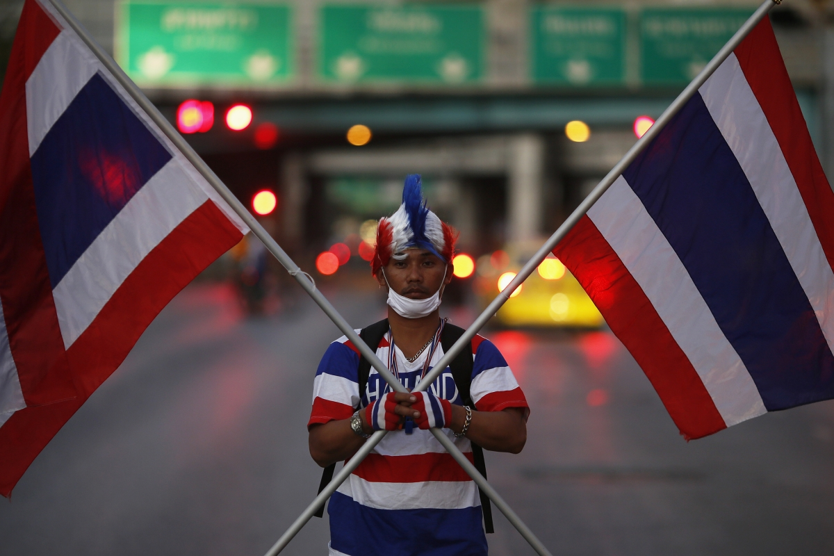 An anti-government protester in the colours of Thailand's national flag arrives to block one of city's the key intersections