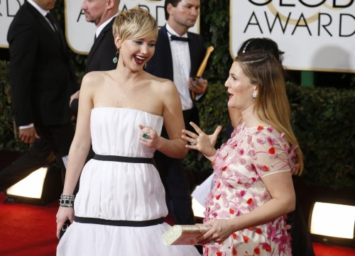 Actresses Jennifer Lawrence and Drew Barrymore arrive at the 71st annual Golden Globe Awards