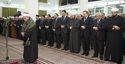 Syrias President Bashar al-Assad 5th R prays during a religious ceremony to commemorate Prophet Mohammads birthday at al-Hamd mosque in Damascus January 12, 2014.