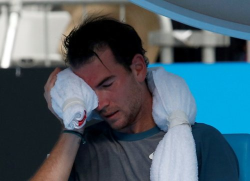 Adrian Mannarino of France holds an ice pack to his face during his men's singles match against David Ferrer of Spain
