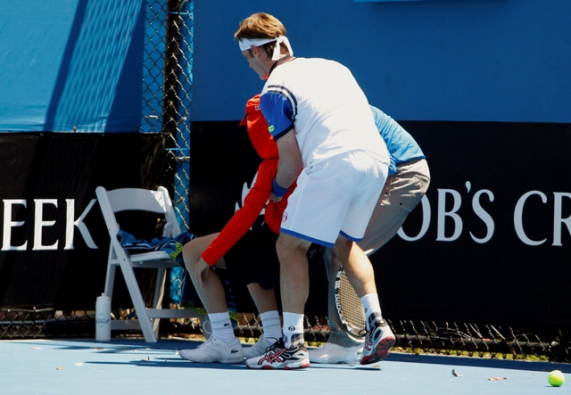 Daniel Gimeno-Traver (front) of Spain assists an official in helping a ball boy who collapsed during his men's singles match against Milos Raonic of Canada at the Australian Open 2014 tennis tournament in Melbourne