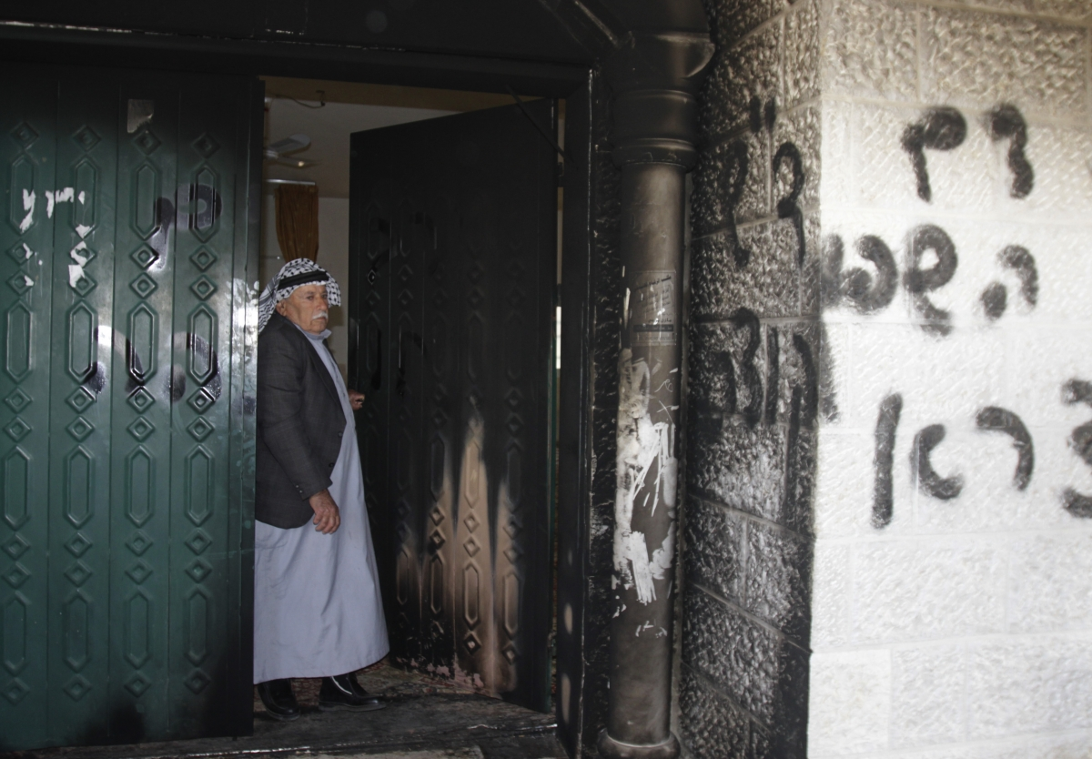 A Palestinian man stands near a door and wall of a mosque which were vandalised in the West Bank village of Deir Istiya