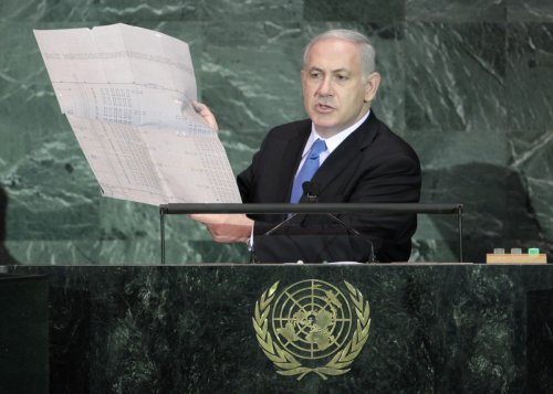 Israeli Prime Minister Benjamin Netanyahu holds up a document outlining plans for the Auschwitz death camp