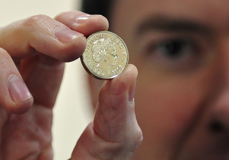 George Osborne holds coin