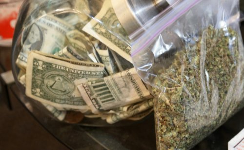 A bag of marijuana being prepared for sale sits next to a money jar at BotanaCare in Northglenn, Colorado