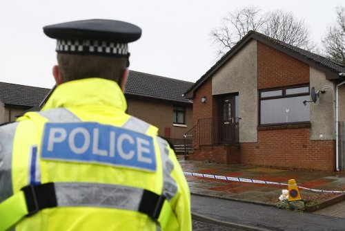 A police officer stands outside a house in Kirkcaldy, Scotland believed to belong to Mikaeel Kular's aunt.