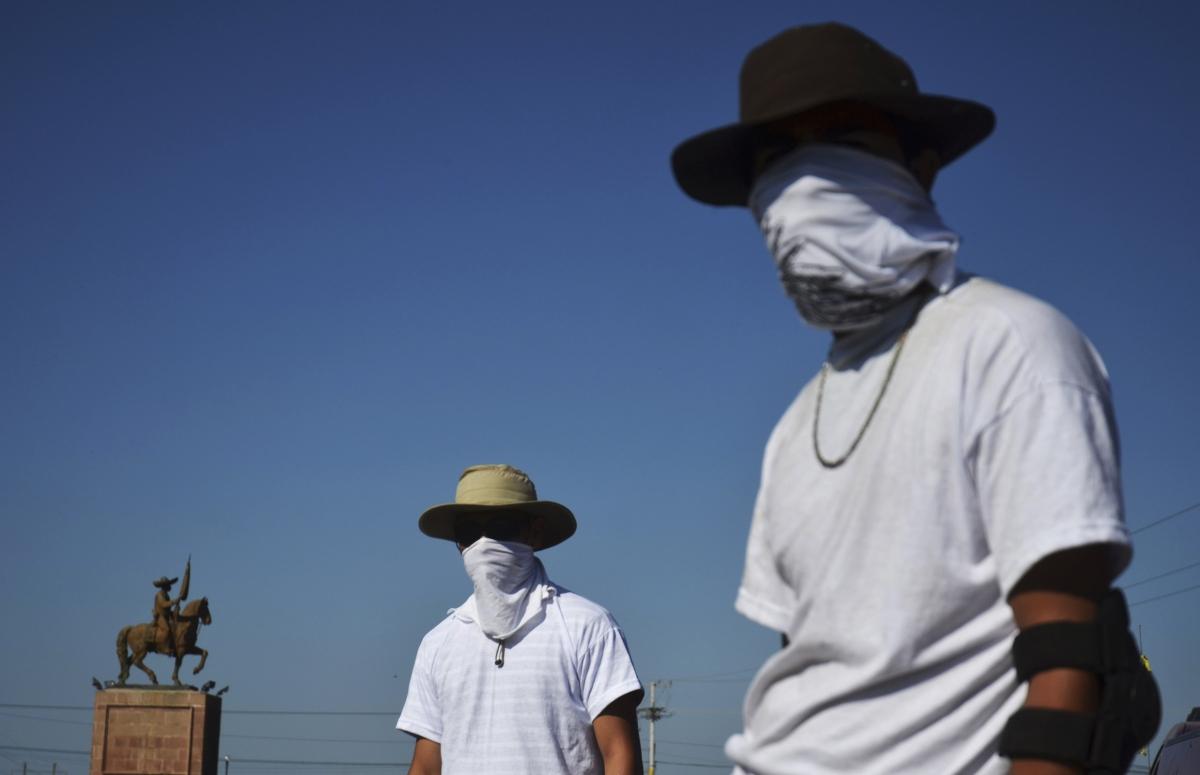 Vigilantes stand at a checkpoint in Mugica near Apatzingan January 14, 2014