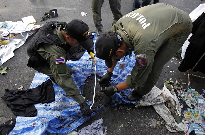 Policemen examine the scene of Sunday's explosion at an anti-government protest in Bangkok.