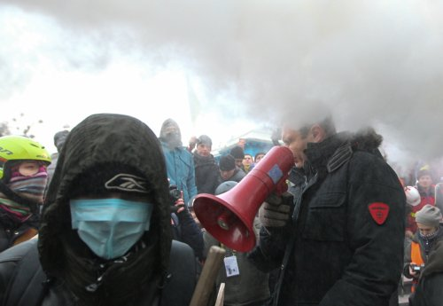 Vitaly KIitschko grimaces as police target him with powder spray during his address to crowds in Kiev