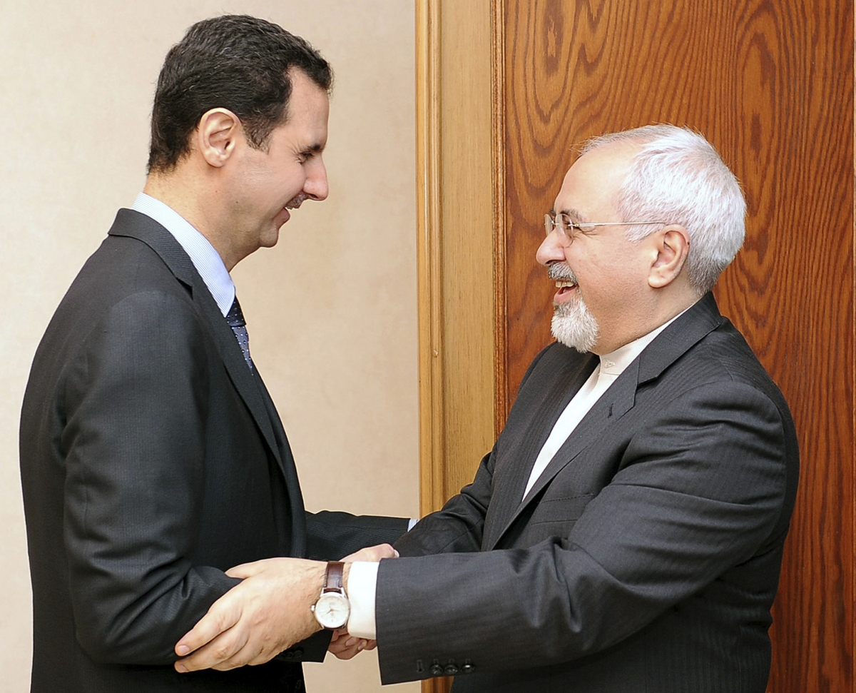 Syria's President Bashar al-Assad (L) welcomes Iran's Foreign Minister Mohammad Javad Zarif before a meeting in Damascus