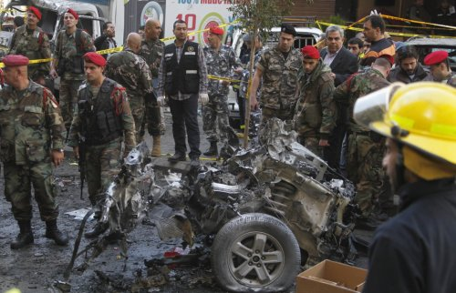 Lebanese army soldiers examine a burnt car at the site of an explosion in the Haret Hreik area