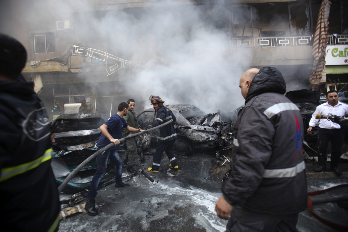 Firefighters extinguish a fire at the site of an explosion in the Haret Hreik area,