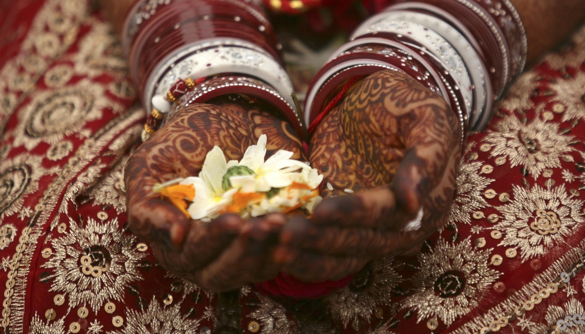 A bride holds flowers with her hands decorated with henna paste during her wedding ceremony in the western Indian city of Ahmedabad.