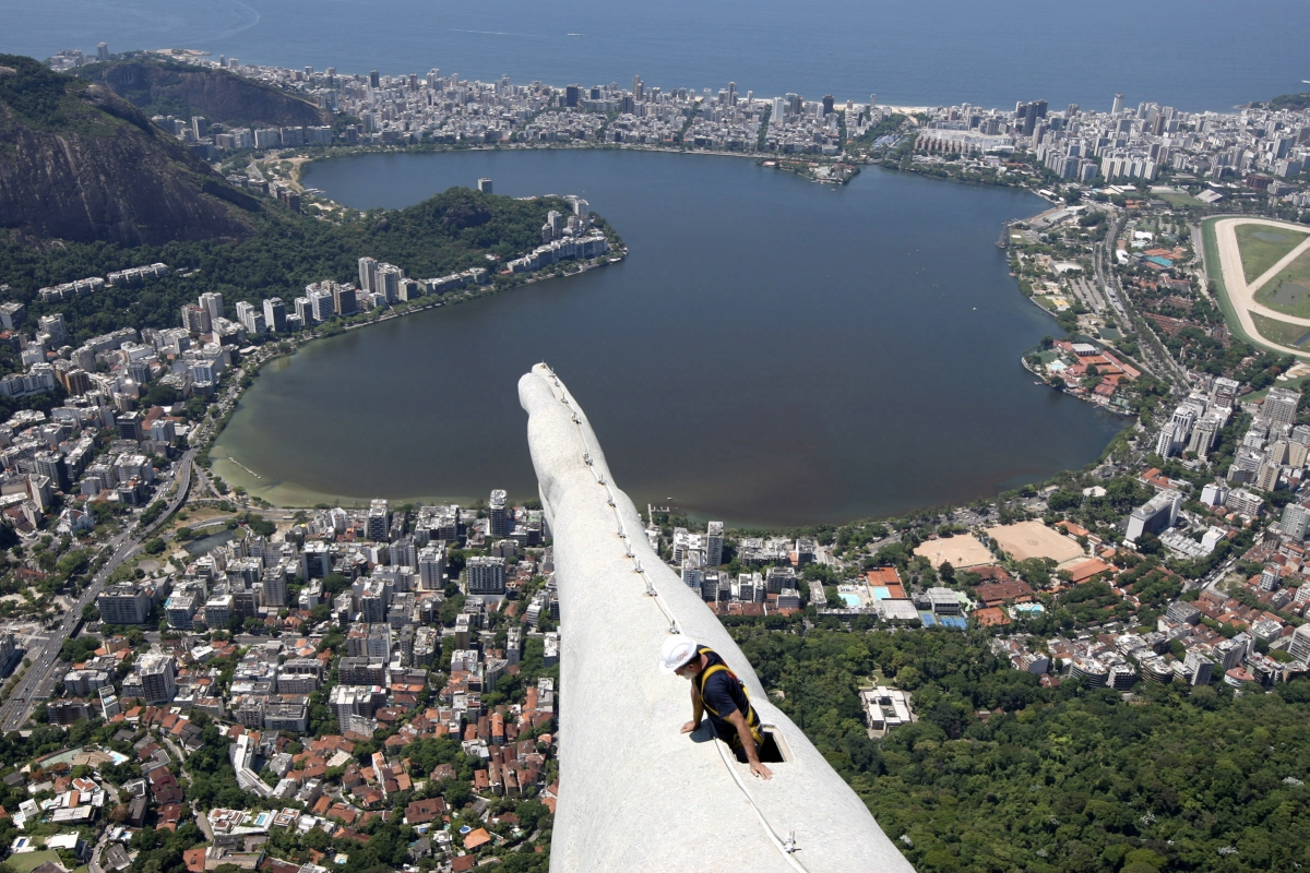 A worker begins work to fix lightning damage to the Christ the Redeemer statue in Rio de Janeiro, after an electrical storm