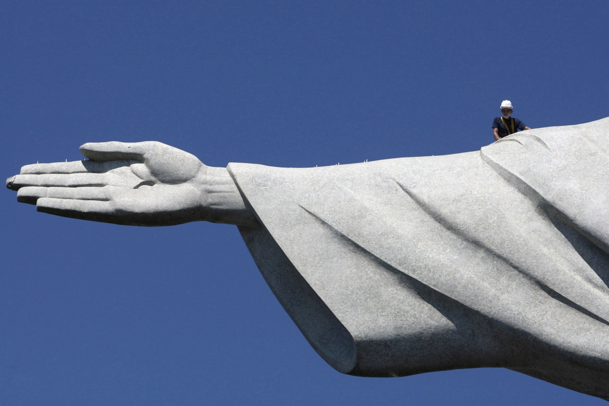 Repair man is dwarfed by huge scale of Christ the Redeemer statue in Rio de Janeiro