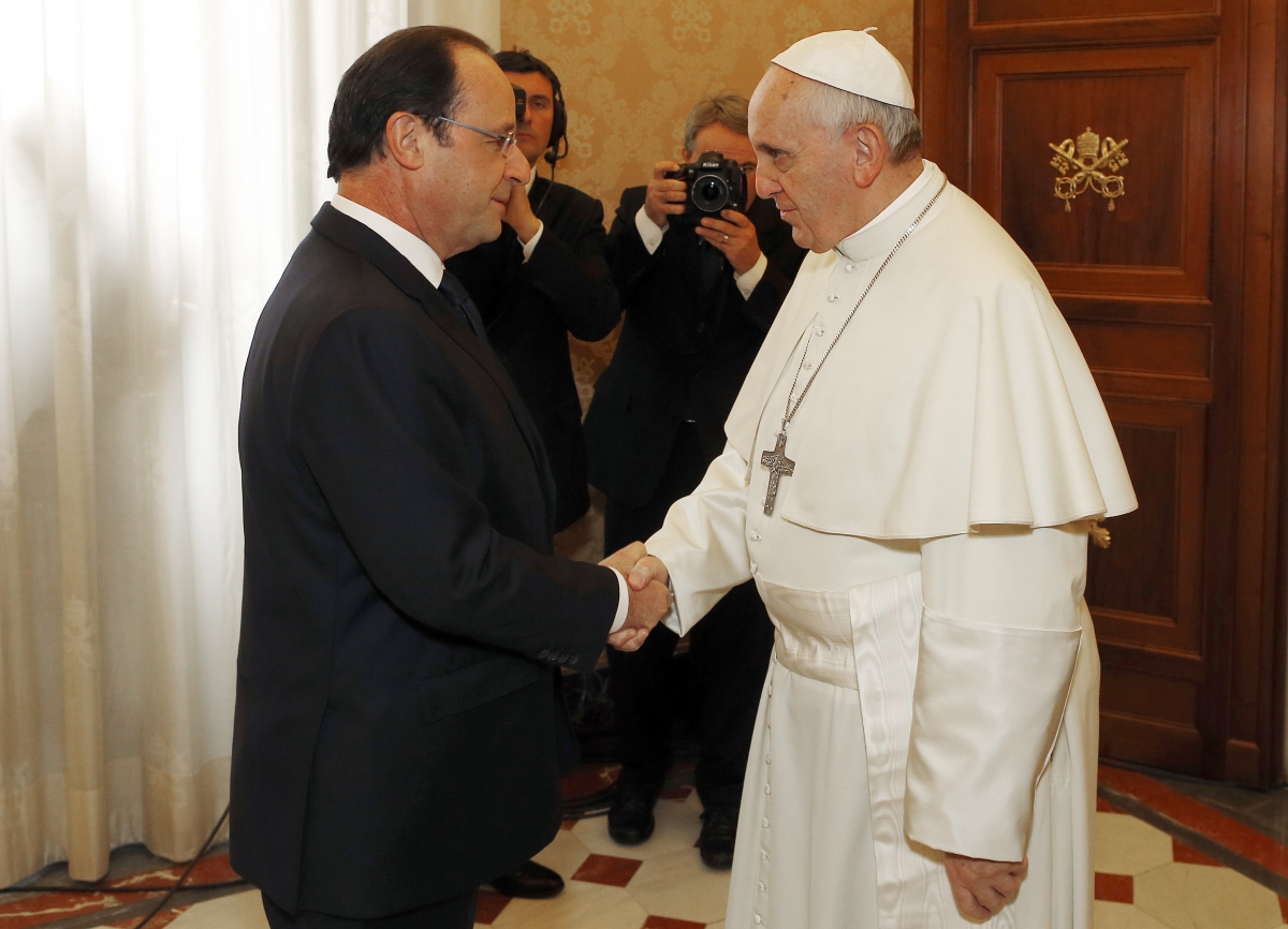 Pope Francis (R) shakes hands with French President Francois Hollande during a private audience at the Vatican
