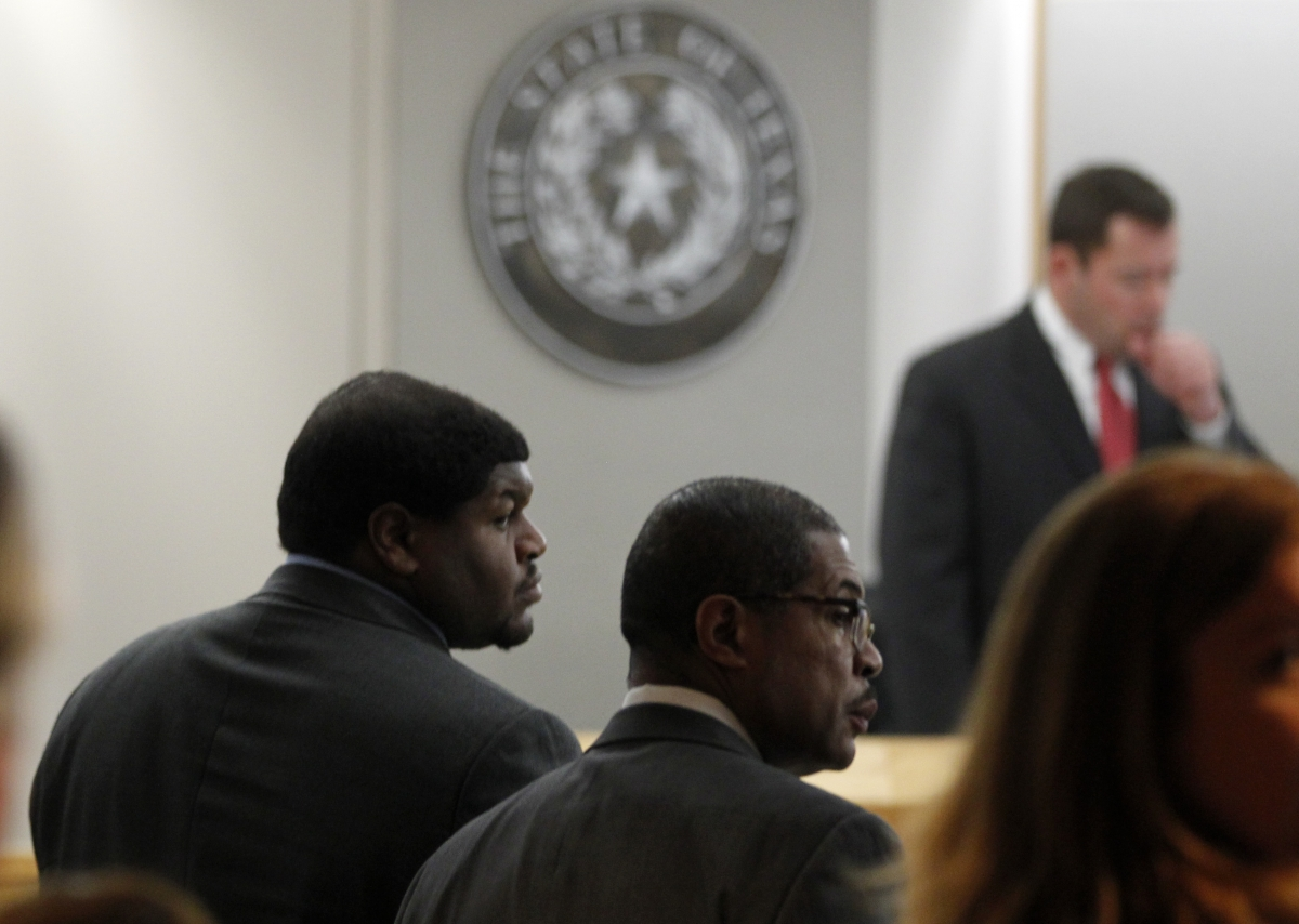 Former Dallas Cowboys player Josh Brent (L) and attorney Kevin Brooks stand in the court room as Judge Robert Burns (standing) presides in Dallas, Texas