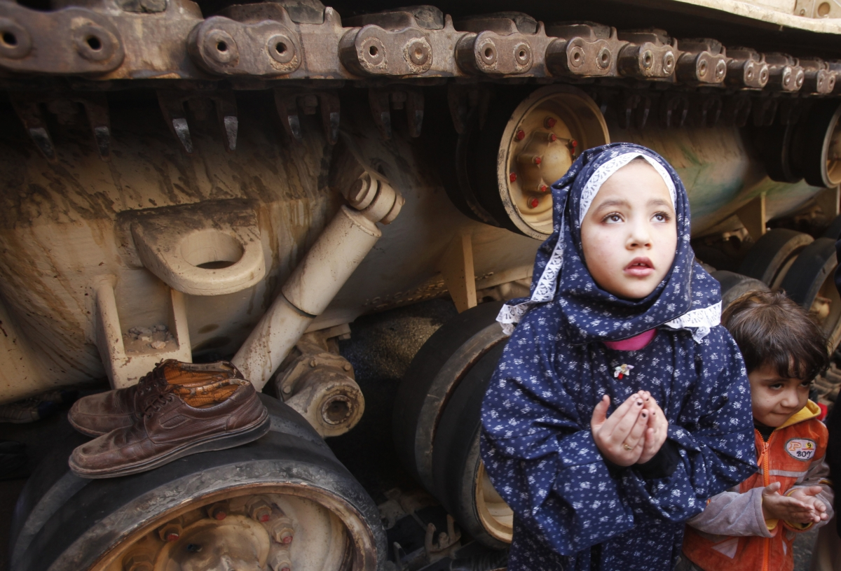 A girl attends Friday prayers in front of an army tank in Tahrir Square in Cairo