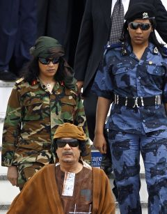 Muammar Gaddafi flanked by two of his female bodyguards on a visit to Rome in 2010.