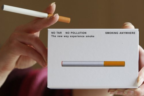 A woman displays a package of E-cigarette.