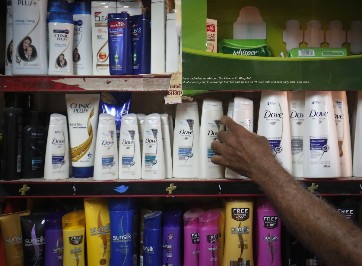A salesman takes a bottle of Hindustan Unilever Limited (HUL) Dove shampoo from a shelf at a shop in Mumbai
