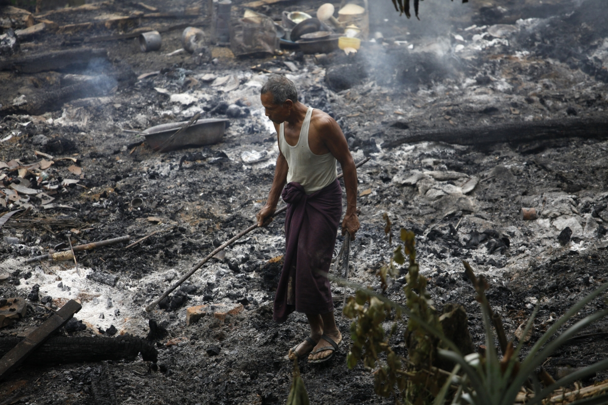 A Muslim man searches for his belongings left behind of his burnt home at Thapyuchai village, outside of Thandwe in the Rakhine state