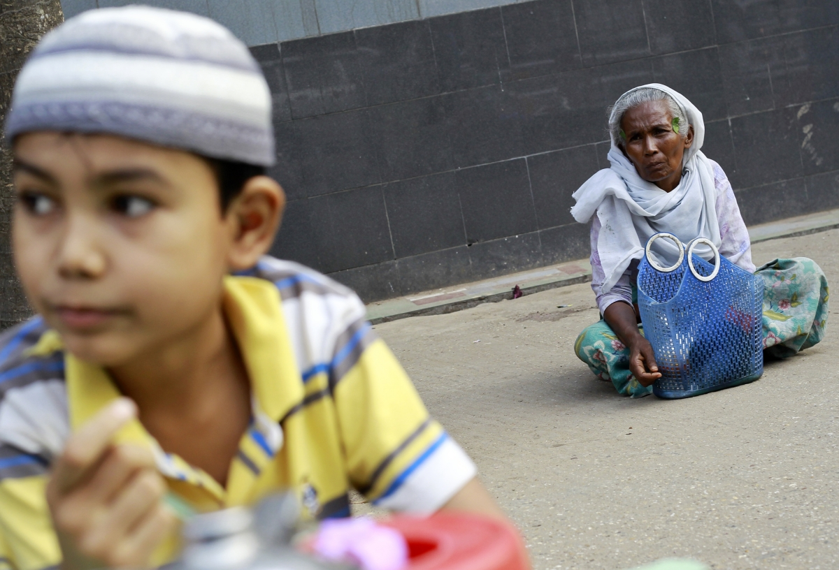A Muslim woman sits near a mosque in Yangon