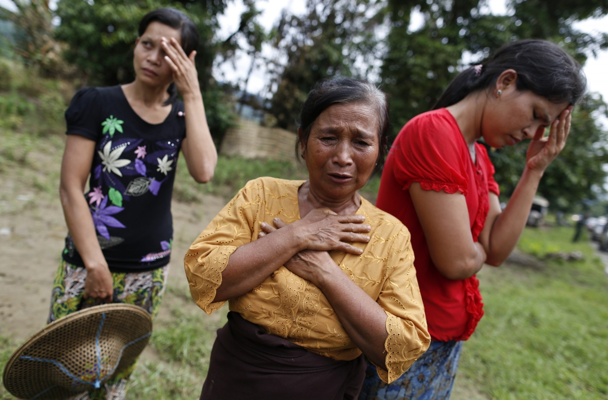 Muslim women react to the loss of their homes which were burnt down in violence in Pauktaw village