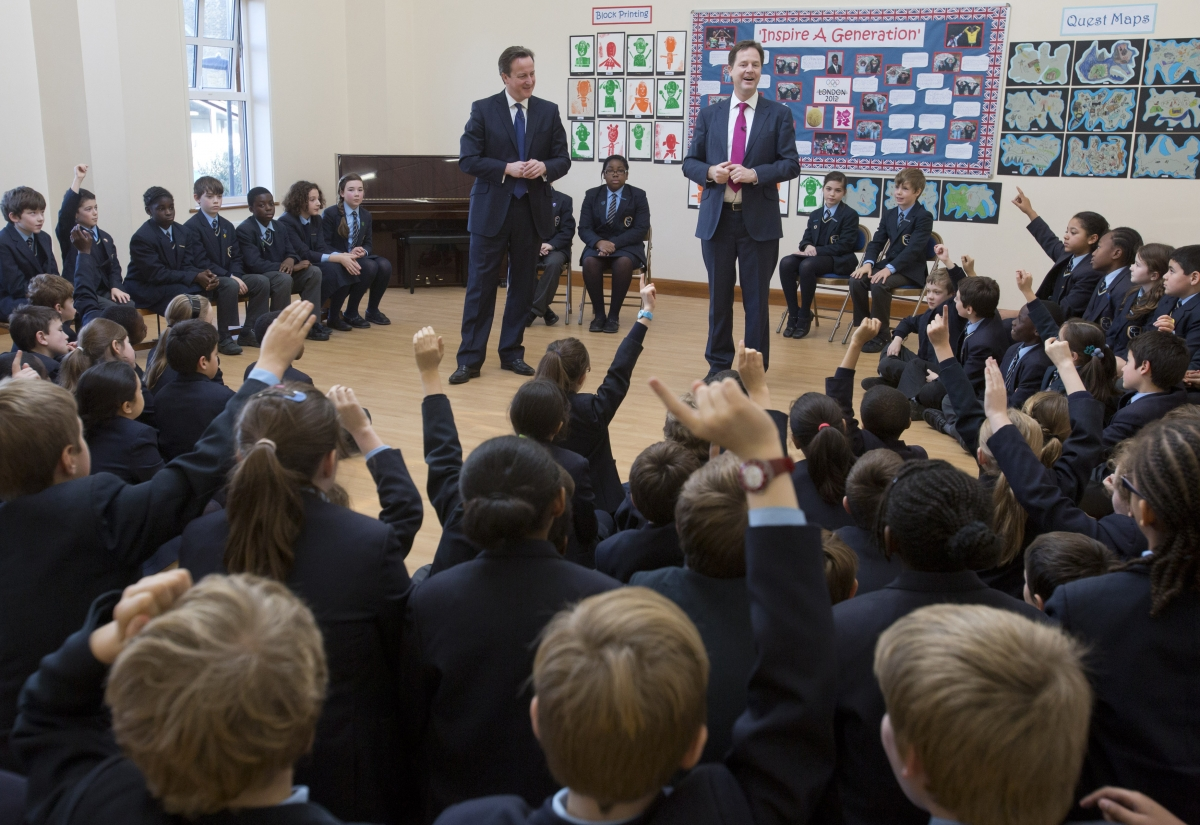 Britain's Prime Minister David Cameron and Deputy Prime Minister Nick Clegg (R) meet children at Corpus Christi Roman Catholic Primary School in Brixton in London