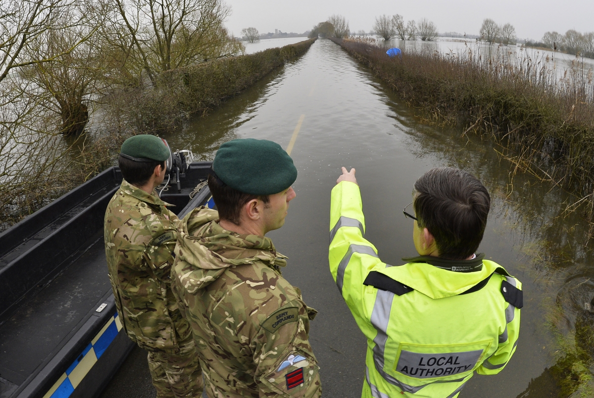 British army Royal Engineers are shown flooded areas by a local official near Muchelney village on the Somerset Levels