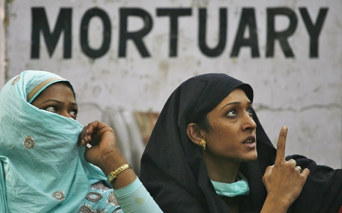 Relatives wait outside a hospital mortuary to pick up the body of the victim.