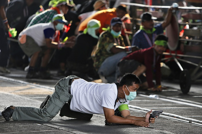 An anti-government protester crawls with a pistol during a gunfight with supporters of the ruling Puea Thai Party.