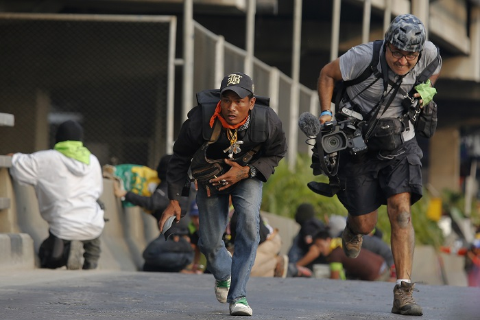 An anti-government protester and a reporter run for cover during a gunfight between government supporters and opponents.