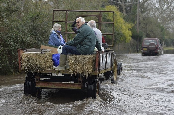 Residents are driven through flooded parts of southwest England on a tractor.