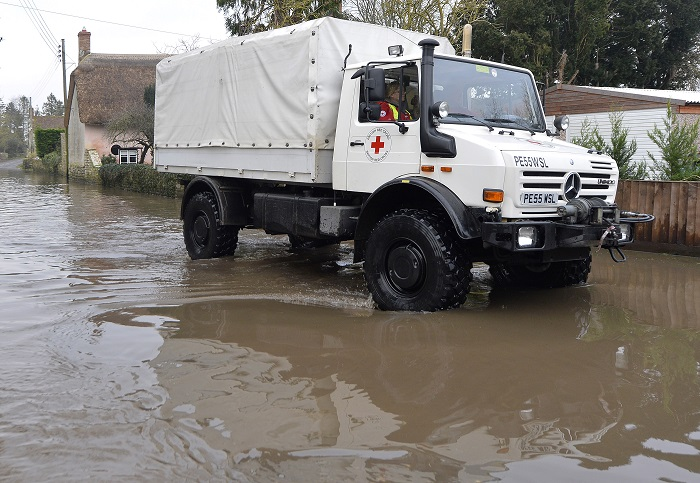 A Red Cross medical supplies vehicle drives through flooded parts of Somerset.