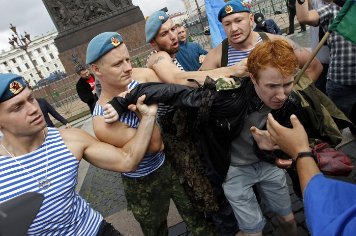 Former Russian paratroopers shove gay rights activist Kirill Kalugin during his one-man protest in St Petersburg.