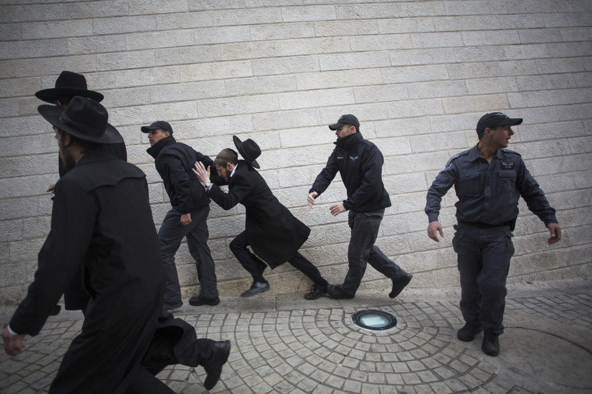 An Israeli policeman pushes an ultra-Orthodox Jewish protester during a demonstration in Jerusalem