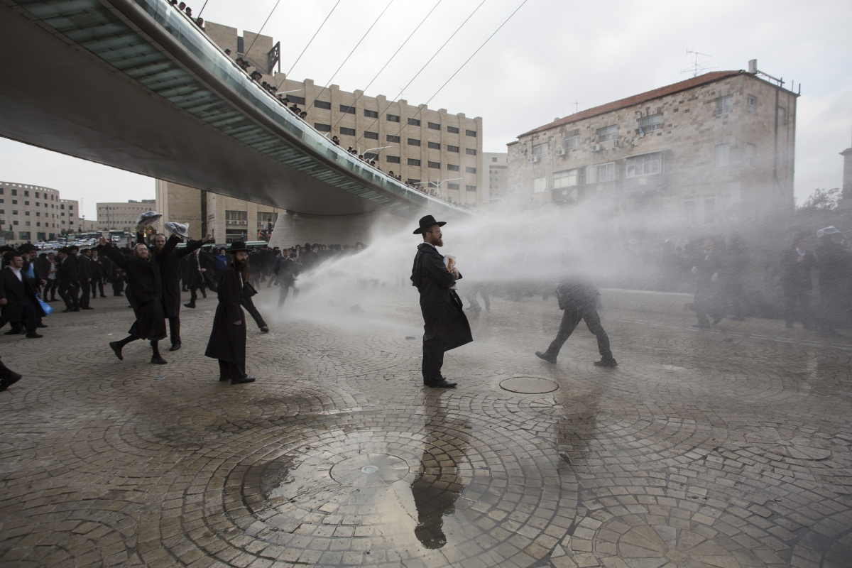 Ultra-Orthodox Jewish protesters are sprayed with a water cannon by Israeli policemen during a demonstration in Jerusalem