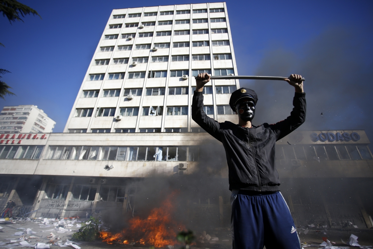 A protester stands near a fire set in front of a government building in Tuzla