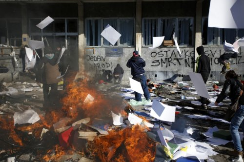 Protesters stand near a fire set in front of a government building in Tuzla