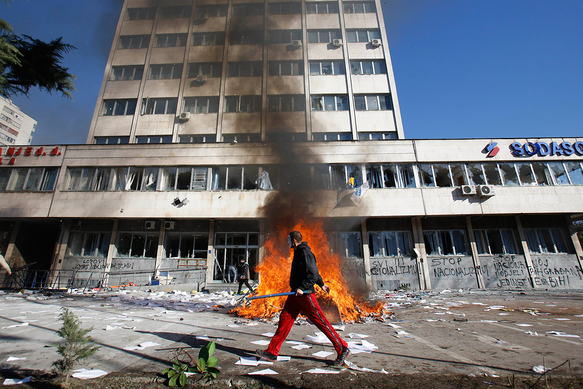 A Bosnian protester walks by a local government building