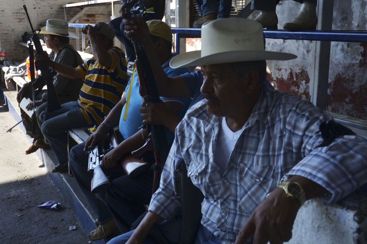 Vigilantes, or members of the community police, line up during a program to register their weapons and create a rural police in Paracuaro in Michoacan state