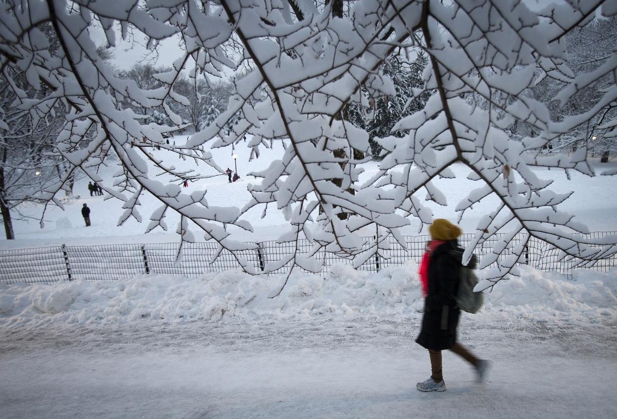 A woman walks through snow in Central Park in the Manhattan borough of New York