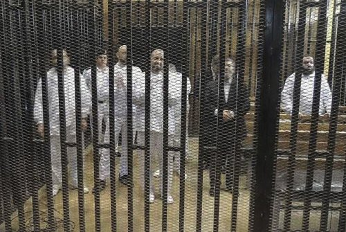 Mohamed Morsi (R) stands with other senior figures of the Muslim Brotherhood in a cage in a courthouse on the first day of their trial.