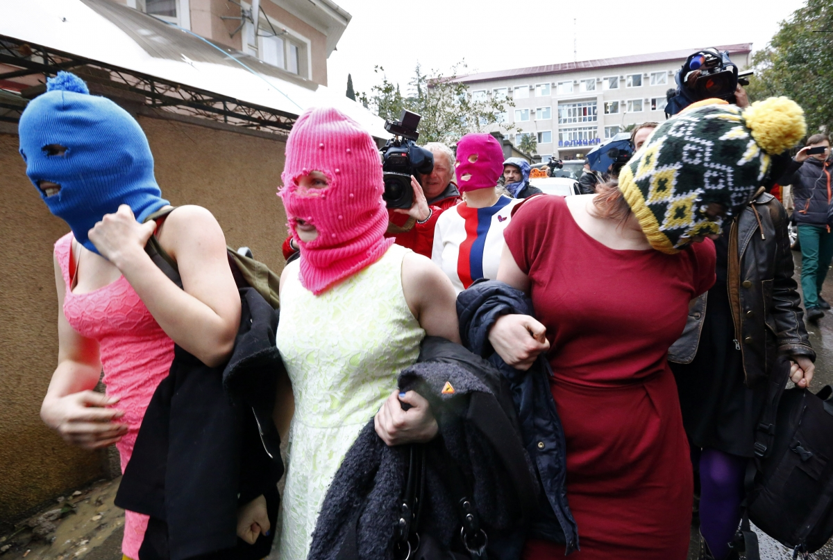 Masked members of protest band Pussy Riot leave a police station in Adler during the 2014 Sochi Winter Olympics