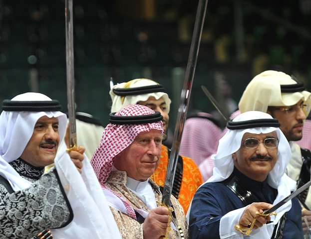 Britain's Prince Charles (C), wearing a traditional Saudi uniform, dances with a sword